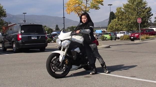 kadın sürücü motosikleti geri itiyor